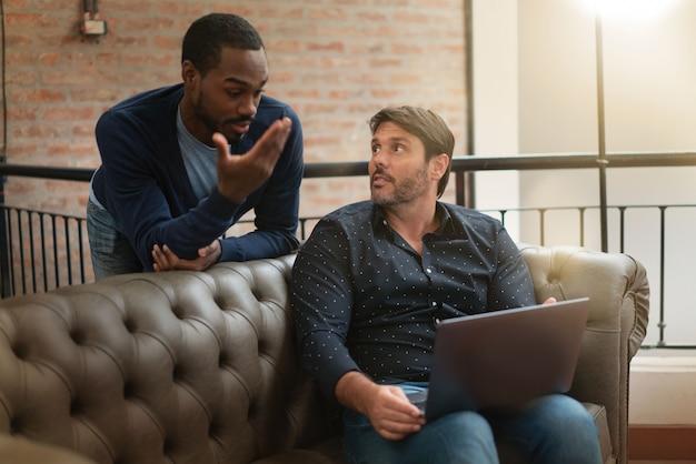 Bemannen sie die mitarbeiter, die beiläufig ideen auf sofa an modernem arbeitsplatz besprechen
