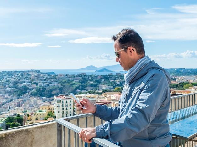 Bemannen sie die tragende sonnenbrille, die auf einer terrasse bei der anwendung seines smartphone steht