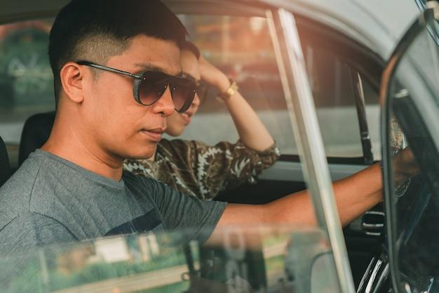 Bemannen sie die tragende sonnenbrille, die autoweinlese mit frau auf straße fährt