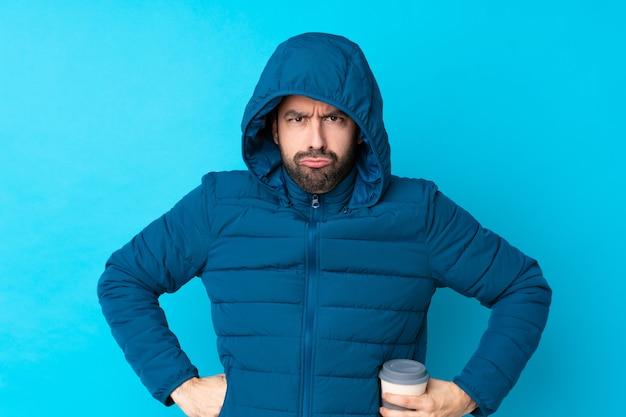 Bemannen sie die tragende winterjacke und das halten eines mitnehmerkaffees über der lokalisierten blauen verärgerten wand