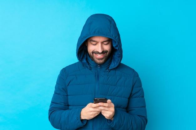 Bemannen sie die tragende winterjacke und das halten eines mitnehmerkaffees über der lokalisierten blauen wand, die eine mitteilung mit dem mobile sendet