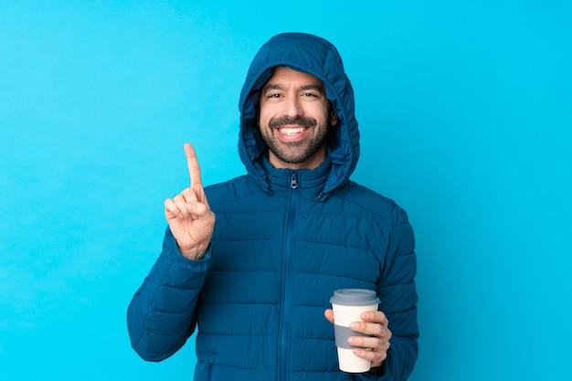 Bemannen sie die tragende winterjacke und das halten eines mitnehmerkaffees über der lokalisierten blauen wand, die einen finger im zeichen des besten zeigt und anhebt