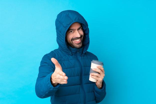 Bemannen sie die tragende winterjacke und das halten eines mitnehmerkaffees über der lokalisierten blauen wand, die hände für das schließen viel rüttelt