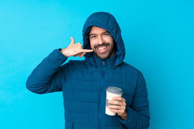 Bemannen sie die tragende winterjacke und das halten eines mitnehmerkaffees über der lokalisierten blauen wand, die telefongeste macht. rufen sie mich zurück zeichen
