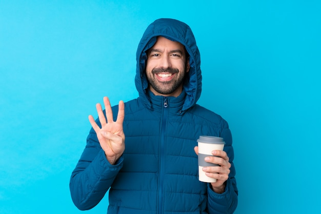 Bemannen sie die tragende winterjacke und das halten eines mitnehmerkaffees über lokalisierter blauer wand, die mit den fingern vier glücklich ist und gezählt ist