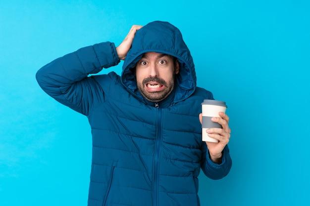 Bemannen sie die tragende winterjacke und das halten eines mitnehmerkaffees über lokalisierter blauer wand frustriert und nimmt hände auf kopf