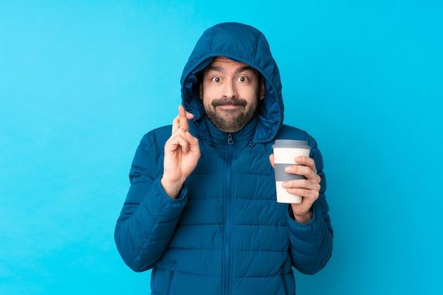 Bemannen sie die tragende winterjacke und das halten eines mitnehmerkaffees über lokalisierter blauer wand mit den fingern, die das beste kreuzen und wünschen