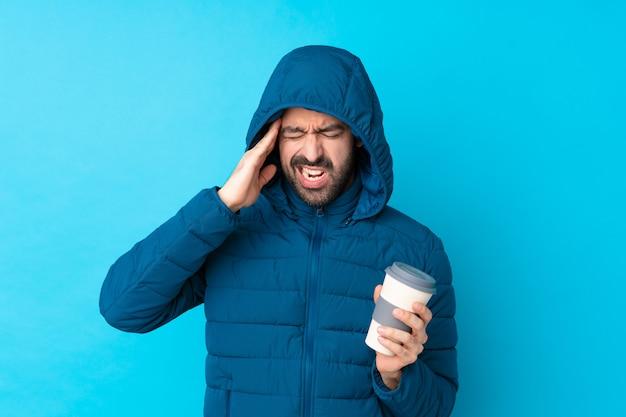 Bemannen sie die tragende winterjacke und das halten eines mitnehmerkaffees über lokalisierter blauer wand mit kopfschmerzen