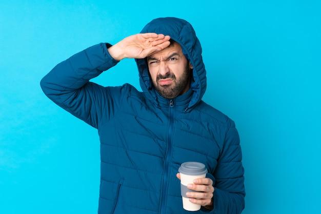 Bemannen sie die tragende winterjacke und das halten eines mitnehmerkaffees über lokalisierter blauer wand mit müdem und krankem ausdruck