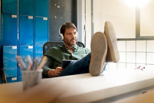 Bemannen sie die tragenden kopfhörer, die im modernen büro mit den füßen oben auf schreibtisch arbeiten