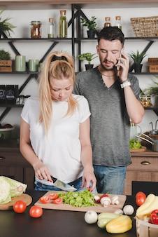 Bemannen sie die unterhaltung am handy, der das frauausschnittgemüse mit messer in der küche betrachtet