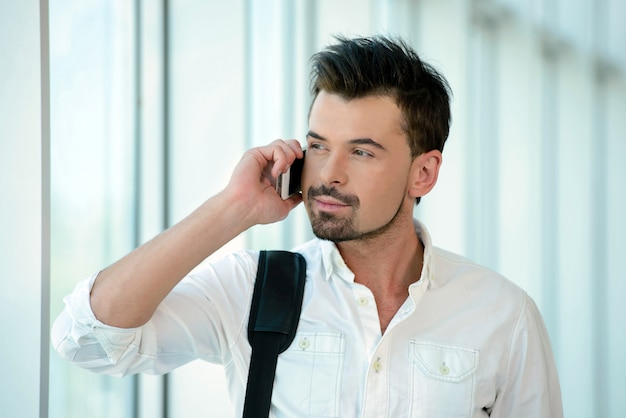 Bemannen sie die unterhaltung am telefonreisen, das nach innen in flughafen geht.