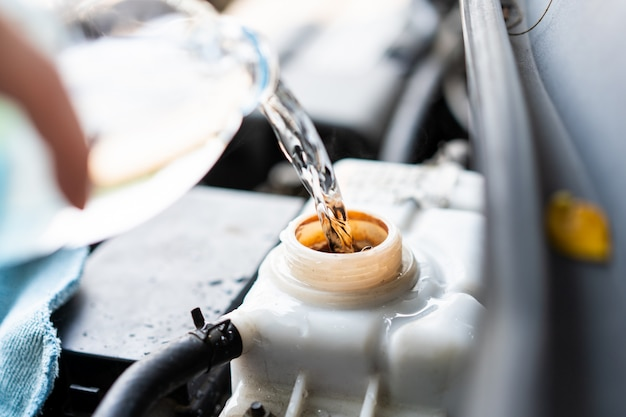 Bemannen sie füllendes wasser in kesseltank in einem fahrzeugabschluß oben.