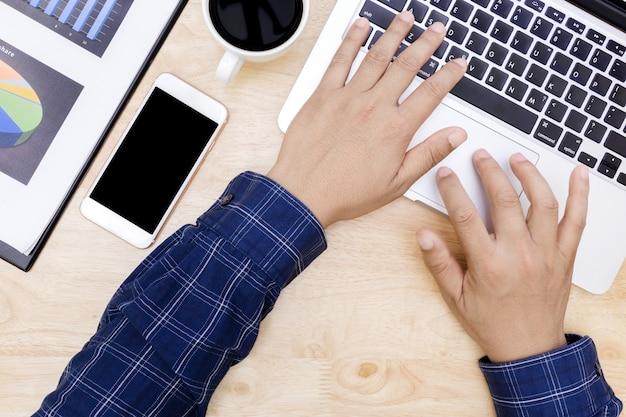Bemannen sie hand auf laptoptastatur mit monitor des leeren bildschirms, das mannarbeitsgeschäft, das an holz arbeitet