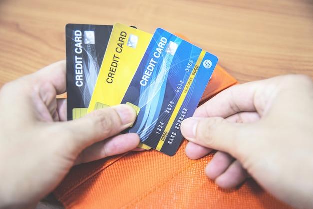 Bemannen sie kreditkarte in der hand halten - online zahlen vom haus oder vom kreditkarten-konzept der erhöhten verbindlichkeiten