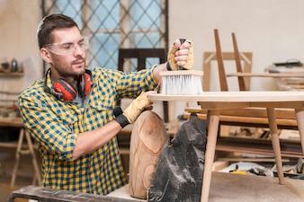 Bemannen Sie Reinigungsholz mit Staubbürste auf hölzerner Planke in der Werkstatt