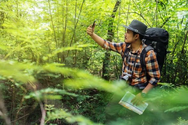 Bemannen sie reisenden mit rucksack unter verwendung des smartphone zum nehmen eines selfie im wald