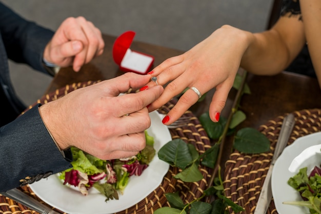 Bemannen sie ring auf frauenfinger bei tisch mit platten und blume setzen