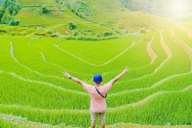 Bemannen sie stellung mit seinem hinteren schönen terassenförmig angelegten reisreisfeld und berglandschaft in sapa vietnam.