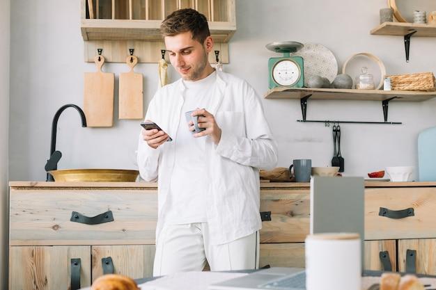 Bemannen sie stellung vor küchenarbeitsplatte unter verwendung des handys, der kaffeetasse hält