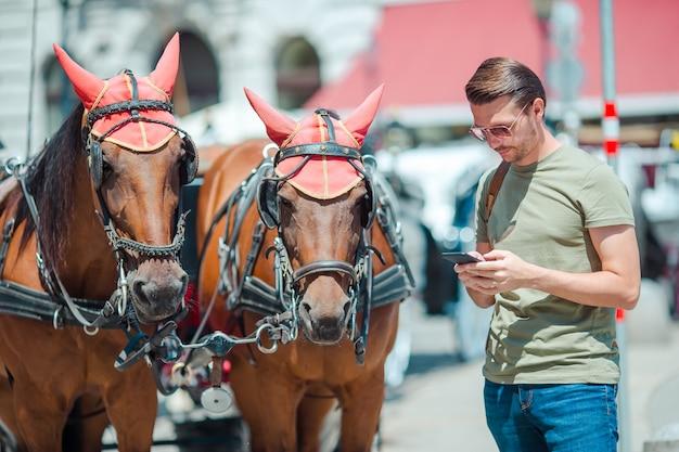 Bemannen sie touristen mit einem stadtplan und einem rucksack in der europa-straße, der kaukasische junge, der mit karte der europäischen stadt schaut,