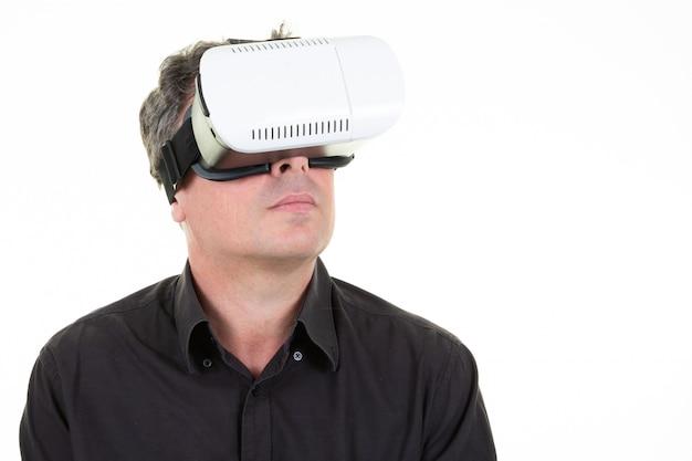 Bemannen sie tragende schutzbrillen der virtuellen realität im weißen studio smartphone unter verwendung mit vr-kopfhörer, der oben schaut