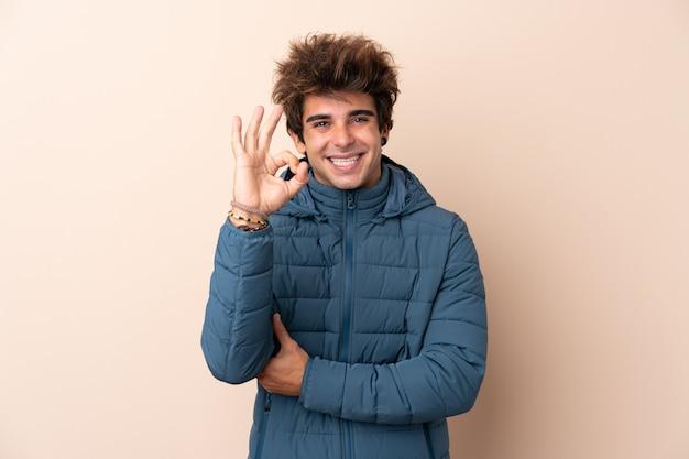 Bemannen sie tragende winterjacke über der lokalisierten wand, die okayzeichen mit den fingern zeigt