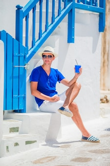 Bemannen sie trinkenden kaffee, um in traditionelles griechisches dorf draußen zu gehen. junge mit heißem kaffee café im im freien in mykonos-stadt.