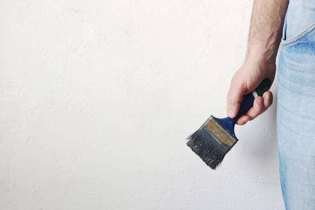Bemannt die hand, die blaue farbe der malerpinselfarbe auf weißer farbwand hält