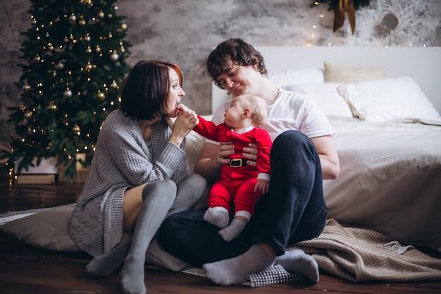 Bemuttern sie baby auf bett nahe weihnachtsbaum zu hause küssen