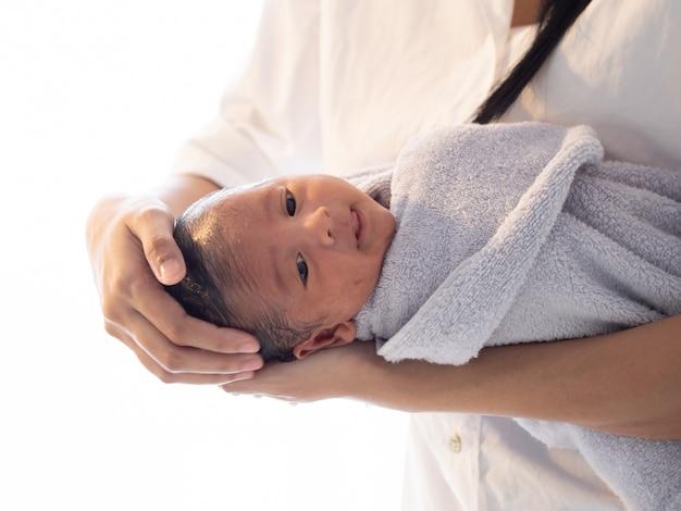 Bemuttern sie das asiatische jungenbaby des bades, das auf der badewanne neugeboren ist
