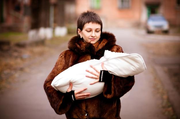 Bemuttern sie das halten des babys auf den armen, eingewickelt in einer decke. weichzeichnungseffekt.