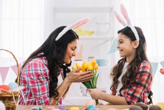 Bemuttern sie das riechen der gelben tulpen, die von ihrer tochter auf ostern-tagesfeier gegeben werden