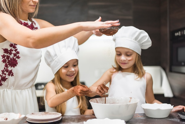 Bemuttern sie das sieben des kakaopulvers mit sieb in der schüssel während glückliche mädchen, die lebensmittel zubereiten