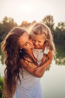 Bemuttern sie das spielen und das haben des spaßes mit tochter durch sommerfluß bei sonnenuntergang. frau, die kind und das lachen hält. familie