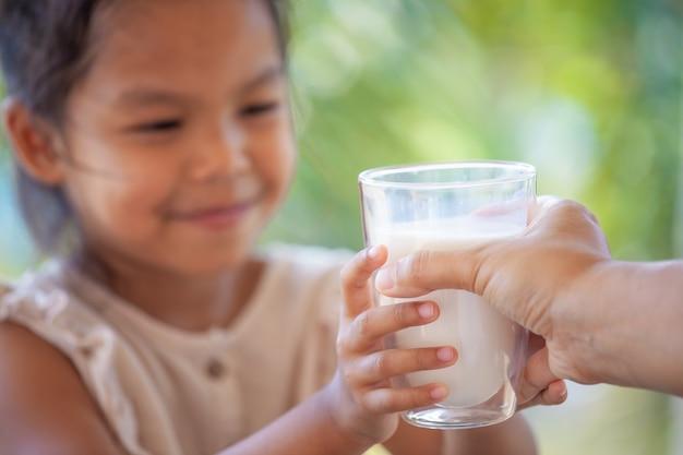 Bemuttern sie die hand, die ihrem kind glas milch sorgfältig und liebe gibt
