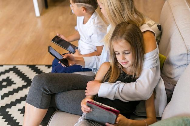 Bemuttern sie und ihre kinder, die ihre hohe ansicht der telefone betrachten