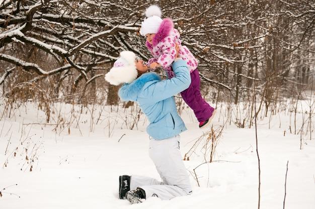 Bemuttern sie und ihre kleine tochter, die schönen wintertag genießt.
