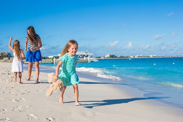 Bemuttern sie und ihre kleinen töchter, die spaß am exotischen strand am sonnigen tag haben