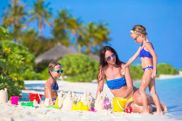 Bemuttern sie und zwei kinder, die mit sand auf tropischem strand spielen