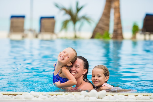 Bemuttern sie und zwei kinder, die sommerferien im luxusswimmingpool genießen