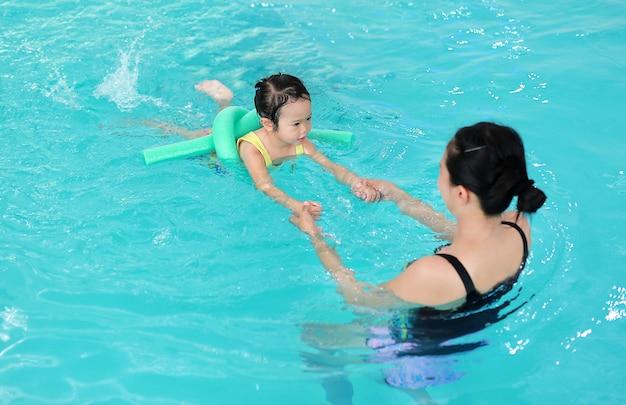 Bemuttern sie unterrichtendes kind im swimmingpool mit schaumnudel