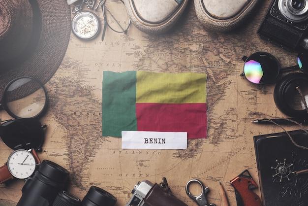 Benin-flagge zwischen dem zubehör des reisenden auf alter weinlese-karte. obenliegender schuss