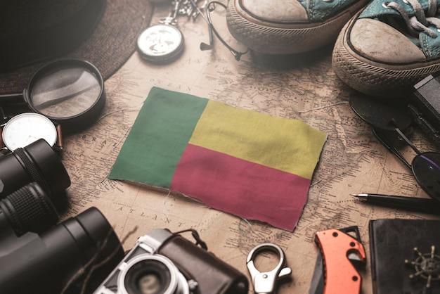Benin-flagge zwischen dem zubehör des reisenden auf alter weinlese-karte. touristisches bestimmungsort-konzept.