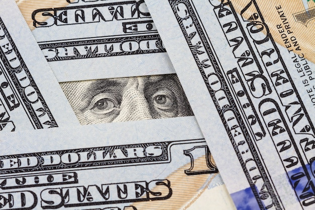 Benjamin franklins augen zwischen hundert dollarnoten
