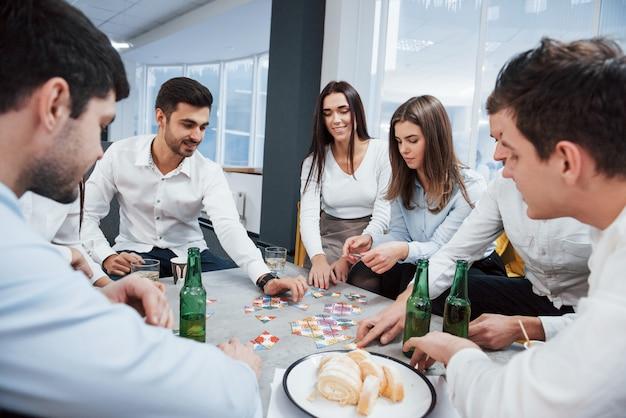 Benötigen sie etwas mehr konzentration. mit dem spiel entspannen. erfolgreiches geschäft feiern. junge büroangestellte sitzen in der nähe des tisches mit alkohol
