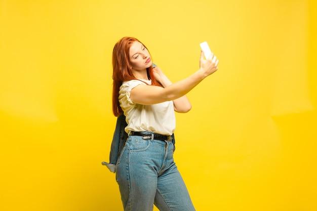 Benötigen sie minimale kleidung für selfie. porträt der kaukasischen frau auf gelbem raum