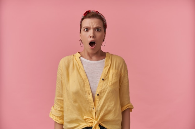 Benommen schockierte junge frau in gelbem hemd mit stirnband am kopf und geöffnetem mund sieht erstaunt aus und schreit über rosa wand