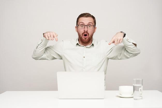 Benommener junger hübscher unrasierter blonder mann, der erstaunlich auf seinem laptop mit zeigefingern zeigt, während er kamera mit großen geöffneten augen betrachtet und über weißem hintergrund posiert