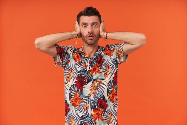 Benommener verängstigter junger mann mit stoppeln im bunten hemd c